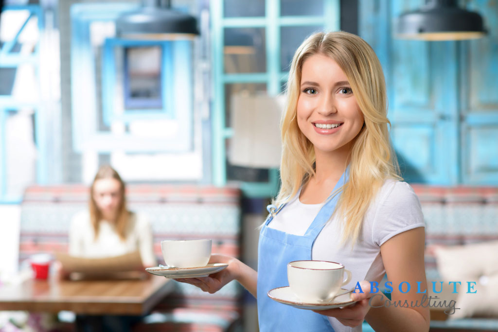 Pleasant waitress holding cup
