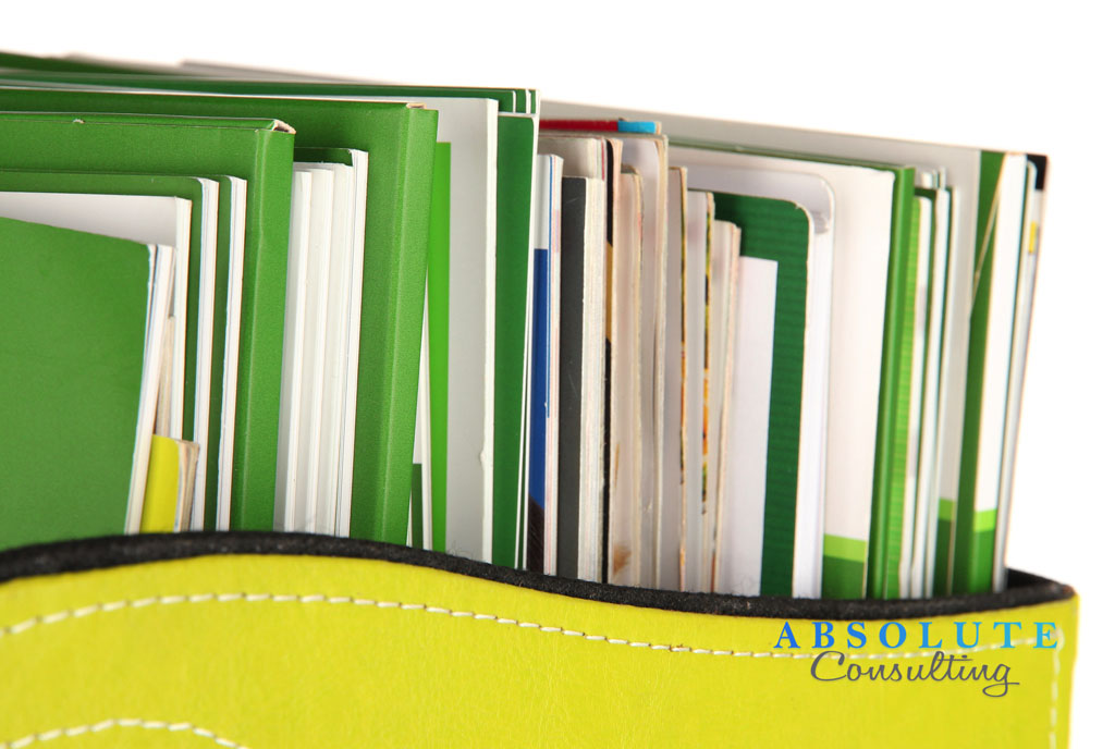 Magazines and folders in green box, isolated on white