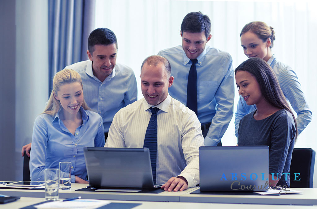 smiling businesspeople with laptops in office